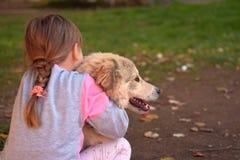 Imagen de la niña que abraza el perro de perrito blanco que pone en la tierra del parque imagenes de archivo