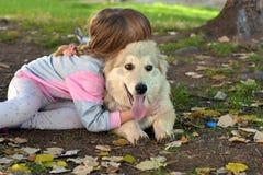 Imagen de la niña que abraza el perro de perrito blanco que pone en la tierra del parque imagen de archivo libre de regalías
