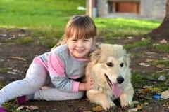 Imagen de la niña que abraza el perro de perrito blanco que pone en la tierra del parque foto de archivo
