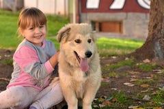 Imagen de la niña que abraza el perro de perrito blanco que pone en la tierra del parque fotografía de archivo libre de regalías