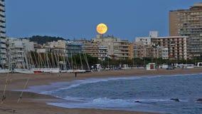 Imagen de la noche del pueblo Palamos (España) con la Luna Llena almacen de metraje de vídeo