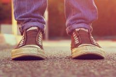 Imagen de la persona con los zapatos sobre la carretera de asfalto Imágenes de archivo libres de regalías