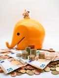 Imagen de la pila de monedas euro con la hucha amarilla en el cierre del fondo para arriba imagenes de archivo