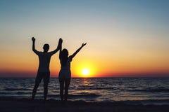 Imagen de la silueta de un par cariñoso que lleva a cabo las manos en la puesta del sol en el mar imagen de archivo
