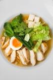 Imagen de la sopa sabrosa con el pollo y del huevo en plato imagenes de archivo