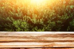 imagen de la tabla de madera en paisaje delantero del bosque en el fondo de la luz de la puesta del sol Foto de archivo