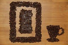 Imagen de la taza de café con los granos de café en la tabla de madera Foto de archivo libre de regalías