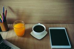 Imagen de la taza de café, tabletas, zumo de naranja en el escritorio Fotografía de archivo
