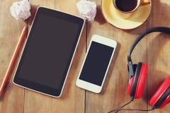 Imagen de la visión superior de la tableta y del smartphone con la pantalla en blanco, los auriculares y la taza de café sobre la Imagen de archivo