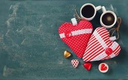 Imagen de la visión superior de los chocolates de la forma del corazón y de las tazas coloridos de los pares de café en fondo de  Fotografía de archivo