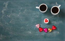 Imagen de la visión superior de los chocolates de la forma del corazón y de las tazas coloridos de los pares de café en fondo de  Foto de archivo libre de regalías