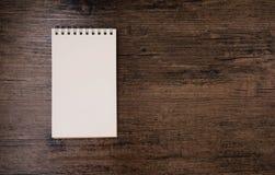 Imagen de la visión superior del cuaderno abierto con la página en blanco en la tabla de madera Imagenes de archivo