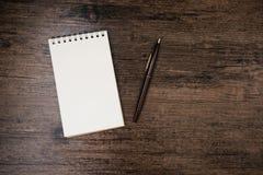 Imagen de la visión superior del cuaderno abierto con la página en blanco y de la pluma en la tabla de madera Fotografía de archivo