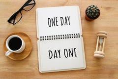 Imagen de la visión superior de la tabla con el cuaderno abierto y el texto un día que da vuelta en el día uno éxito y concepto p Imágenes de archivo libres de regalías