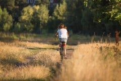 Imagen de la vista posterior de la bicicleta joven del montar a caballo del adolescente en la trayectoria en el campo Fotos de archivo libres de regalías