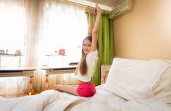 Imagen de la vista posterior del adolescente sonriente que estira en cama en la mañana Imagenes de archivo