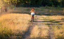 Imagen de la vista posterior de la mujer joven con la bicicleta larga del montar a caballo del pelo en el campo Fotografía de archivo libre de regalías