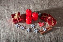 Imagen de las decoraciones de la Navidad, velas, regalos en el fondo de lino fotografía de archivo libre de regalías