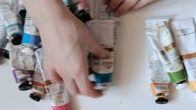 Imagen de las pinturas de la mujer en lona con las pinturas de aceite en su estudio 4k metrajes