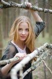 Imagen de las ramas conmovedoras del abedul de la muchacha rubia Fotografía de archivo libre de regalías