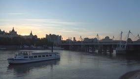 Imagen de Londres con un puente y un barco turístico colocados en el río Támesis