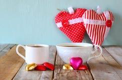 Imagen de los chocolates de la forma del corazón de la remolque y de las tazas rojos de los pares de café en la tabla de madera C Imagen de archivo libre de regalías