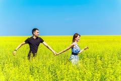 Imagen de los pares felices que corren en prado amarillo Fotos de archivo