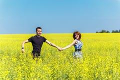Imagen de los pares felices que corren en prado amarillo Foto de archivo