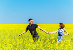 Imagen de los pares felices que corren en prado amarillo Imagen de archivo libre de regalías