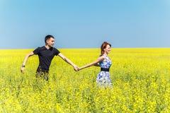 Imagen de los pares felices que corren en prado amarillo Imagenes de archivo