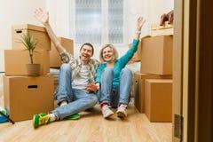 Imagen de los pares felices que se sientan en el sofá entre las cajas de cartón imagen de archivo libre de regalías