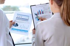 Imagen de los socios comerciales que discuten los documentos, gráficos en el meeti fotos de archivo