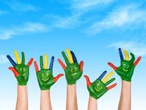 Imagen de manos humanas en pintura colorida con sonrisas en el backgr Fotografía de archivo