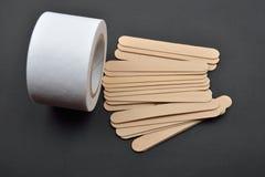 Imagen de muchas espátulas de madera y del rollo del papel para el depila de la cera Fotos de archivo
