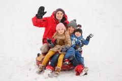 Imagen de padres felices con la hija y el hijo que se sientan en la tubería en invierno Fotografía de archivo libre de regalías