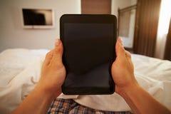 Imagen de Point of View del hombre en la cama que mira la tableta de Digitaces Fotografía de archivo