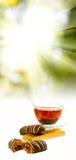 Imagen de tazas con té y caramelos en el primer del fondo de la luz del sol Fotos de archivo