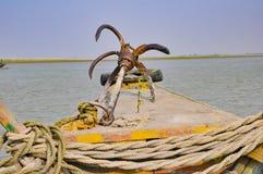 Imagen de un ancla en el frente de un barco en un río con cuerdas y un neumático imágenes de archivo libres de regalías