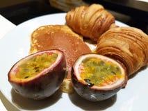 Imagen de un desayuno fresco con la fruta de la pasión, las crepes y los pasteles franceses foto de archivo libre de regalías