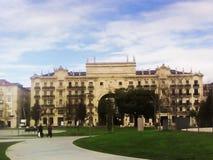 Imagen de un edificio de la cinco-historia contra un cielo azul y un césped verde grande fotografía de archivo libre de regalías