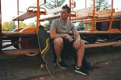 Imagen de un hombre con el longboard que va en el camino Fotografía de archivo libre de regalías