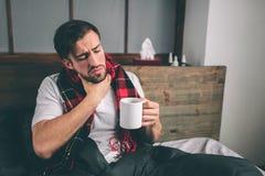 Imagen de un hombre joven con el pañuelo El individuo enfermo miente en cama y tiene mocos el hombre hace una curación para el ca Fotografía de archivo