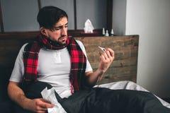 Imagen de un hombre joven con el pañuelo El individuo enfermo miente en cama y tiene mocos el hombre hace una curación para el ca Imagen de archivo
