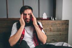 Imagen de un hombre joven con el pañuelo El individuo enfermo miente en cama y tiene mocos el hombre hace una curación para el ca Foto de archivo