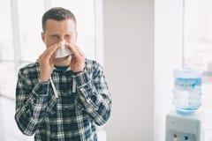 Imagen de un hombre joven con el pañuelo El individuo enfermo tiene mocos hace la curación para el frío común Fotografía de archivo