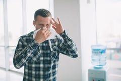 Imagen de un hombre joven con el pañuelo El individuo enfermo tiene mocos hace la curación para el frío común Imágenes de archivo libres de regalías