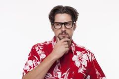 Imagen de un hombre joven en la camisa hawaiana que presenta con la mano en la barbilla fotos de archivo libres de regalías