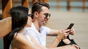 Imagen de un par alegre usando smartphones en el parque almacen de metraje de vídeo