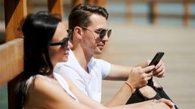 Imagen de un par alegre usando smartphones en el parque metrajes