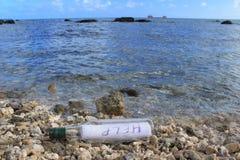 Botella con el mensaje de la AYUDA Fotografía de archivo